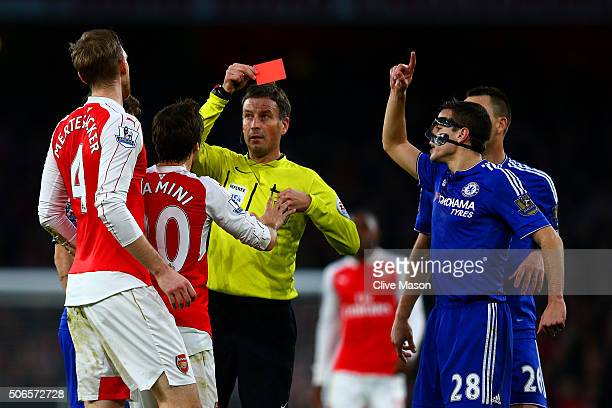 Referee Mark Clattenburg shows a red card to Per Mertesacker of Arsenal during the Barclays Premier League match between Arsenal and Chelsea at...