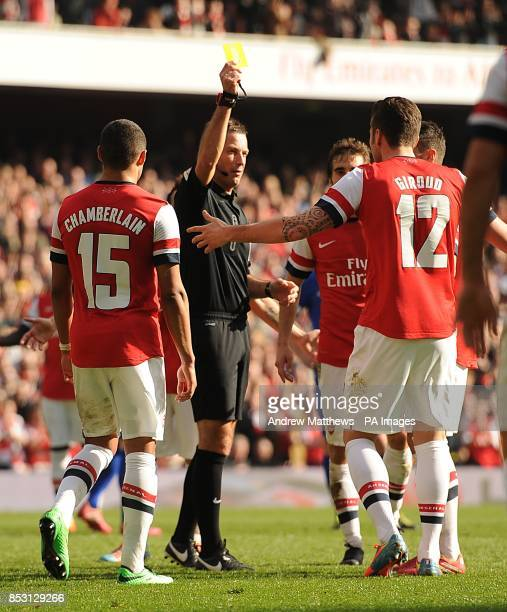 Referee Mark Clattenburg shows a yellow card to Arsenal's Olivier Giroud for encroaching during Mikel Arteta's first penalty