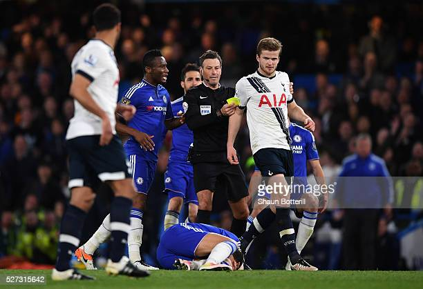 Referee Mark Clattenburg shows a yellow card to Eric Dier of Tottenham Hotspur after bringing down Eden Hazard of Chelsea during the Barclays Premier...