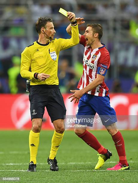 Referee Mark Clattenburg shows a yellow card to Gabi of Atletico Madrid as he complains about a decision during the UEFA Champions League Final match...