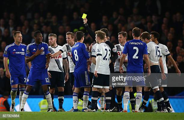 Referee Mark Clattenburg shows a yellow card to John Mikel Obi of Chelsea during the Barclays Premier League match between Chelsea and Tottenham...