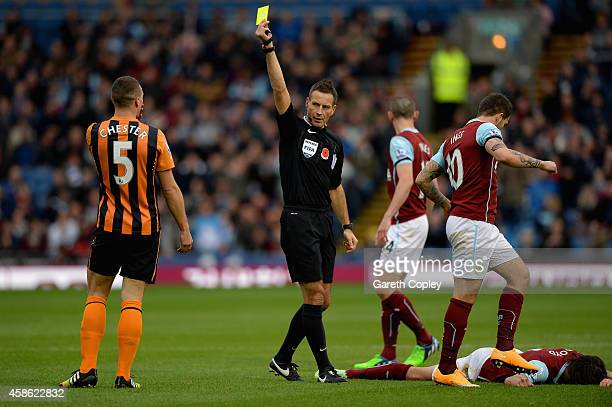 Referee Mark Clattenburg shows James Chester of Hull City a yellow card during the Barclays Premier League match between Burnley and Hull City at...