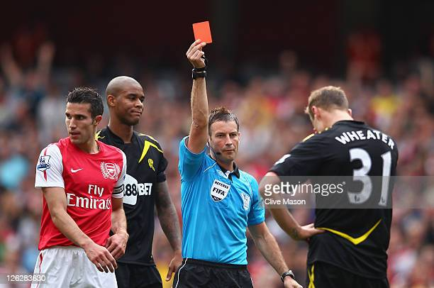 Referee Mark Clattenburg shows the red card to David Wheater of Bolton Wanderers during the Barclays Premier League match between Arsenal and Bolton...