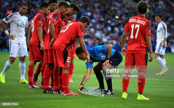Referee Mark Clattenburg sprays some vanishing spray on the pitch during the UEFA Super Cup Final at the Cardiff City Stadium Cardiff