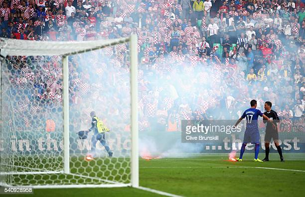 Referee Mark Clattenburg talks to Mario Mandzukic of Croatia as flares are thrown onto the pitch during the UEFA EURO 2016 Group D match between...