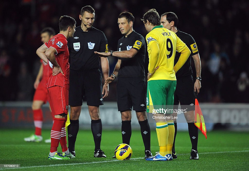 Referee Mark Clattenburg tosses the coin with captains Adam Lallana of Southampton and Grant Holt of Norwich during the Barclays Premier League match between Southampton and Norwich City at St Mary's Stadium on November 28, 2012 in Southampton, England.