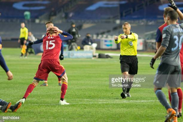 Referee Mark Geiger points to the penalty spot as Justen Glad of Real Salt Lake reacts to the decision after a foul on Maximiliano Moralez of New...