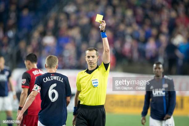 Referee Mark Geiger shows the yellow card to Scott Caldwell of New England Revolution during the New England Revolution Vs Toronto FC regular season...
