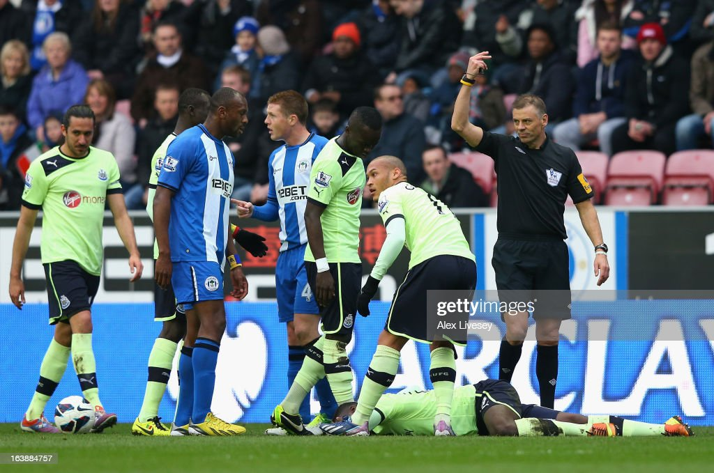 Referee Mark Halsey gestures to the bench as Massadio Haidara of Newcastle United lies injured during the Barclays Premier League match between Wigan Athletic and Newcastle United at the DW Stadium on March 17, 2013 in Wigan, England.