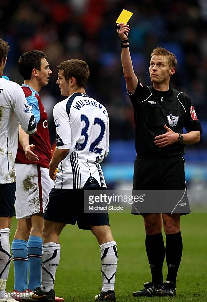 Referee Mark Jones shows the yellow card to Jack Wilshere of Bolton after an end of match scuffle during the Bolton Wanderers and Aston Villa...