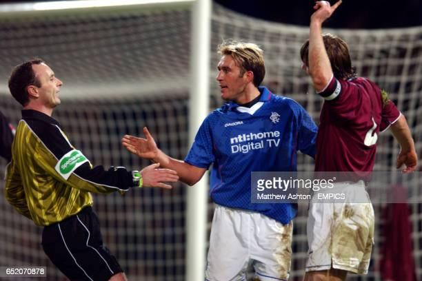 Referee Mark McCurry runs over to calm a situation between Rangers' Fernando Ricksen and Heart Of Midlothian's Steven Pressley