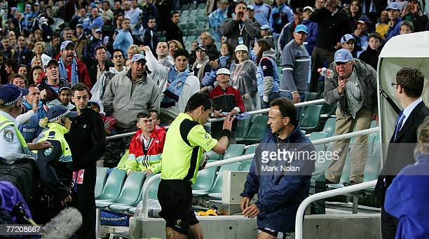 Referee Mark Sheild is pelted with bottles as he leaves the field with a police escort after the round seven ALeague match between Sydney FC and the...