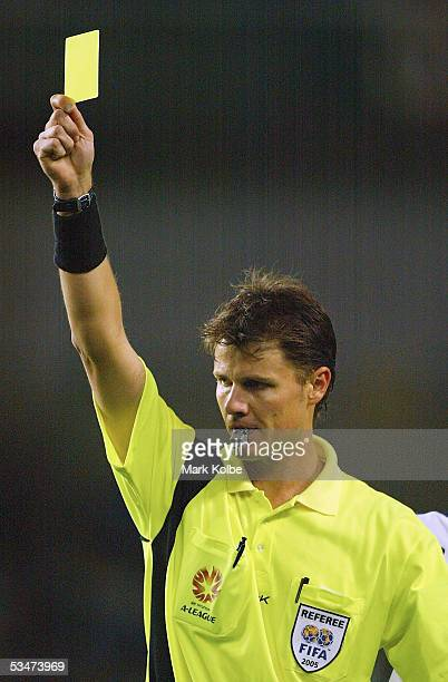 Referee Mark Shield gives out a yellow card during the round one ALeague match between the Sydney FC and Melbourne Victory at Aussie Stadium on...