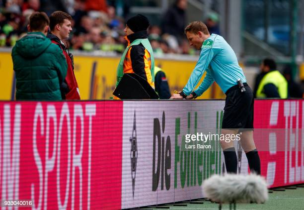 Referee Markus Petersen looks on the video assistant screen during the Bundesliga match between Borussia Moenchengladbach and TSG 1899 Hoffenheim at...