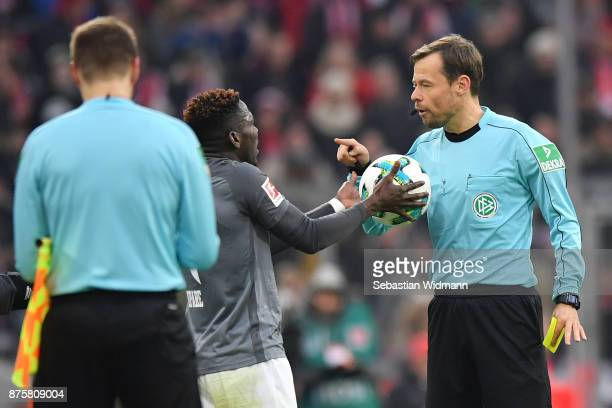 Referee Markus Schmidt argues with Daniel Opare of Augsburg during the Bundesliga match between FC Bayern Muenchen and FC Augsburg at Allianz Arena...