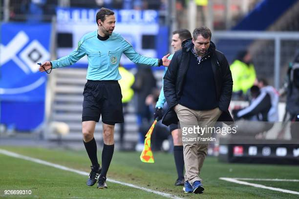 Referee Markus Schmidt explains to Bernd Hollerbach, coach of Hamburg, why a goal Hamburg scored was later disallowed after video review, during the...