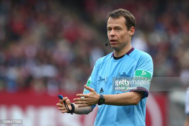 Referee Markus Schmidt holds the ball during the German Bundesliga match between FC Nuernberg and Hamburger SV in Nuremberg Germany 06 October 2013...