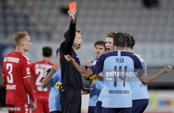 Referee Markus Schmidt shows a red card to Alassane Plea of Moenchengladbachduring the Bundesliga match between Sport-Club Freiburg and Borussia...