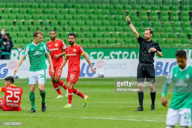 Referee Markus Schmidt shows Christian Gross of SV Werder Bremen the yellow card during the Bundesliga match between SV Werder Bremen and Bayer 04...