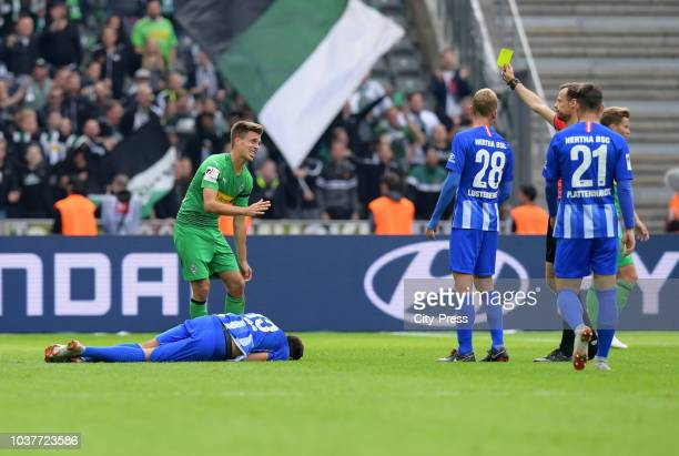 Referee Markus Schmidt shows Patrick Herrmann of Borussia Moenchengladbach the yellow card during the game between Hertha BSC and Borussia...
