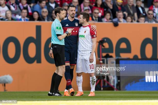Referee Markus Schmidt speaks with Sandro Wagner of Muenchen and Daniel Baier of Augsburg during the Bundesliga match between FC Augsburg and FC...