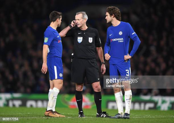 Referee Martin Atkinson awaits the VAR decision during the Carabao Cup SemiFinal First Leg match between Chelsea and Arsenal at Stamford Bridge on...