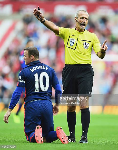 Referee Martin Atkinson awards a free kick after a challenge on Wayne Rooney of Manchester United during the Barclays Premier League match between...