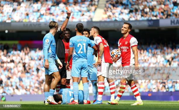 Referee Martin Atkinson awards Granit Xhaka of Arsenal a red card during the Premier League match between Manchester City and Arsenal at Etihad...