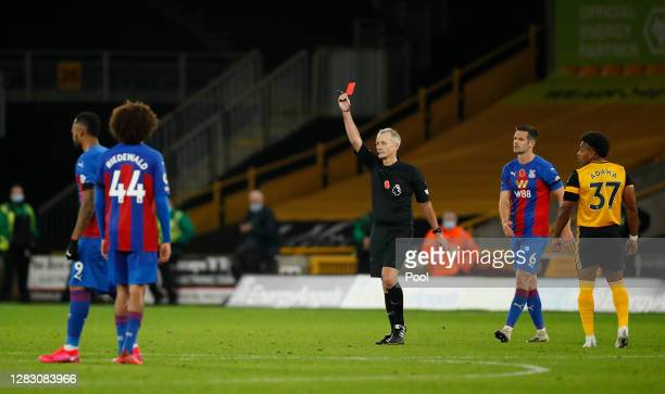 Referee Martin Atkinson awards Luka Milivojevic of Crystal Palace a red card following a VAR review during the Premier League match between...