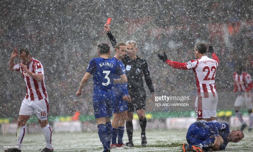 TOPSHOT - Referee Martin Atkinson (C) awards Stoke City's Scottish midfielder Charlie Adam (L) a red card as Everton's English striker Wayne Rooney (R) clutches his leg during the English Premier League football match between Stoke City and Everton at the Bet365 Stadium in Stoke-on-Trent, central England on March 17, 2018. / AFP PHOTO / Roland Harrison / RESTRICTED TO EDITORIAL USE. No use with unauthorized audio, video, data, fixture lists, club/league logos or 'live' services. Online in-match use limited to 75 images, no video emulation. No use in betting, games or single club/league/player publications. /