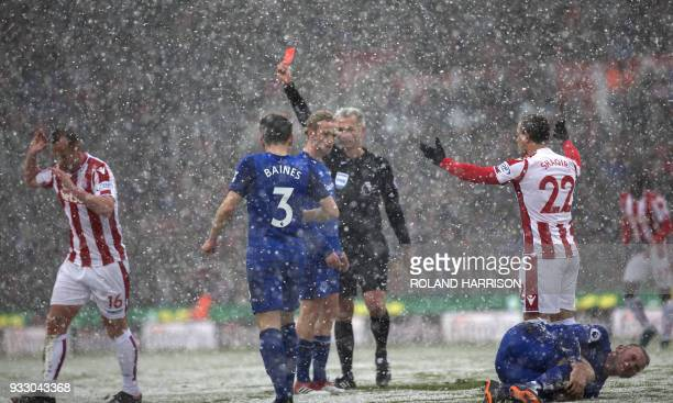 Referee Martin Atkinson awards Stoke City's Scottish midfielder Charlie Adam a red card as Everton's English striker Wayne Rooney clutches his leg...