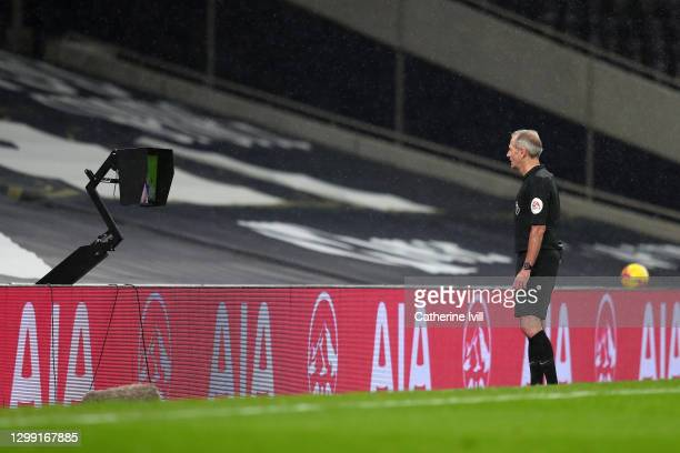 Referee Martin Atkinson checks the VAR screen to see if Mohamed Salah of Liverpool goal which later leads to it being disallowed stands during the...