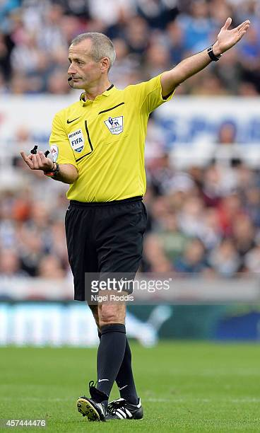 Referee Martin Atkinson gestures during the Premier League football match between Newcastle United and Leicester City at St James' Park on October 18...