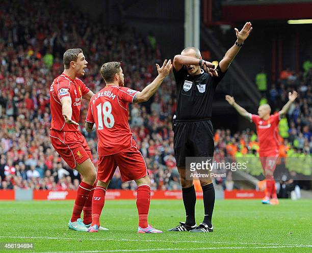 Referee Martin Atkinson gestures towards Jordan Henderson and Alberto Moreno of Liverpool during the Barclays Premier League match between Liverpool...