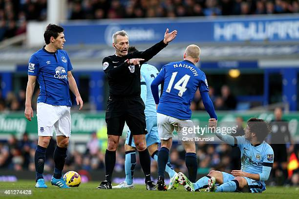 Referee Martin Atkinson gives a decision during the Barclays Premier League match between Everton and Manchester City at Goodison Park on January 10...