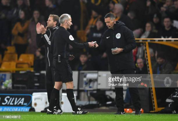 Referee Martin Atkinson hands an object thrown from the stands to the fourth official during the Premier League match between Wolverhampton Wanderers...