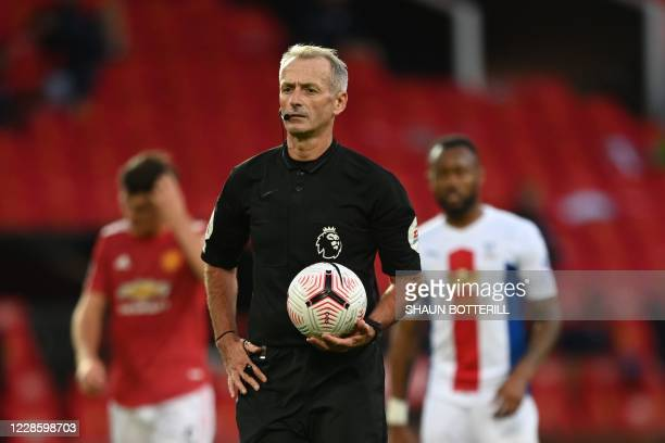 Referee Martin Atkinson holds the ball after he ordered a penalty retaken during the English Premier League football match between Manchester United...