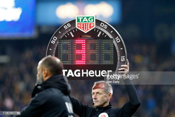 Referee Martin Atkinson holds the board up for extra time during the Premier League match between Huddersfield Town and Wolverhampton Wanderers at...
