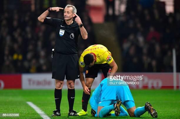 Referee Martin Atkinson indicates a potential head injury to Watford's Brazilian goalkeeper Heurelho Gomes during the English Premier League football...