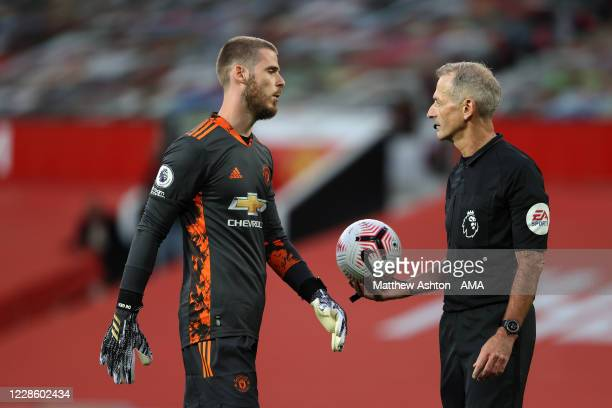 Referee Martin Atkinson informs David De Gea of Manchester United that he moved off his line and Crystal Palace have to retake their penalty kick...