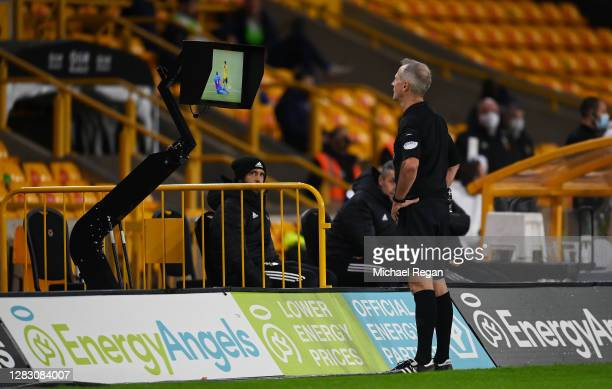 Referee Martin Atkinson looks at the VAR pitch side display before awarding Luka Milivojevic of Crystal Palace a red card during the Premier League...
