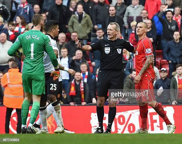 Referee Martin Atkinson separates Manchester United's Spanish goalkeeper David de Gea and Liverpool's Slovakian defender Martin Skrtel during the...