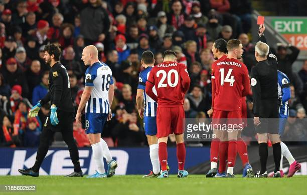 Referee Martin Atkinson shows a red card to Liverpool's Brazilian goalkeeper Alisson Becker during the English Premier League football match between...
