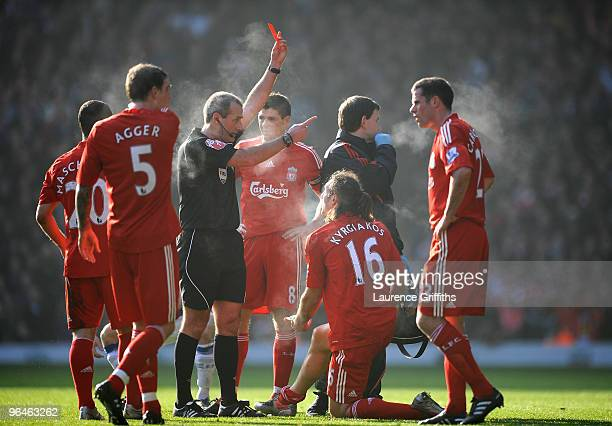 Referee Martin Atkinson shows a red card to Sotiros Kyrgiakos of Liverpool during the Barclays Premier League match between Liverpool and Everton at...