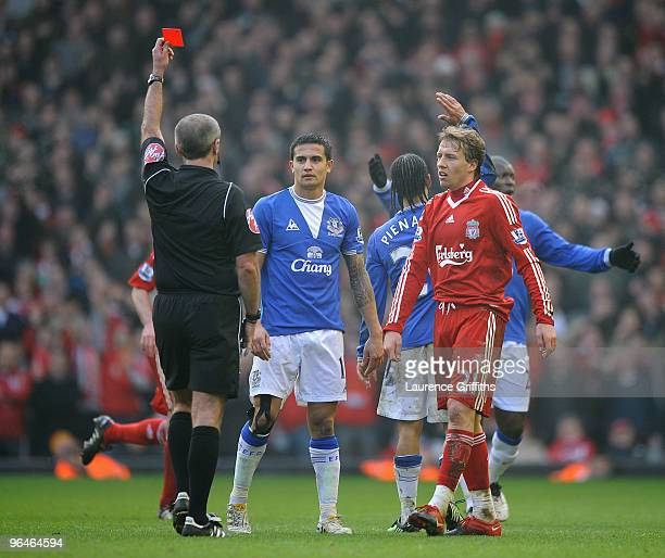 Referee Martin Atkinson shows a red card to Steven Pienaar of Everton during the Barclays Premier League match between Liverpool and Everton at...