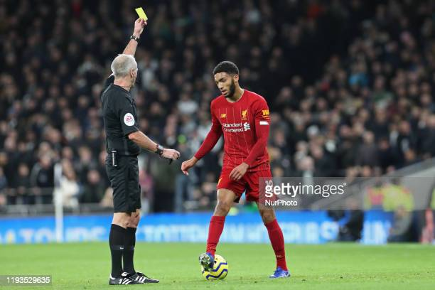 Referee Martin Atkinson shows a yellow card to Liverpool defender Joe Gomez during the Premier League match between Tottenham Hotspur and Liverpool...