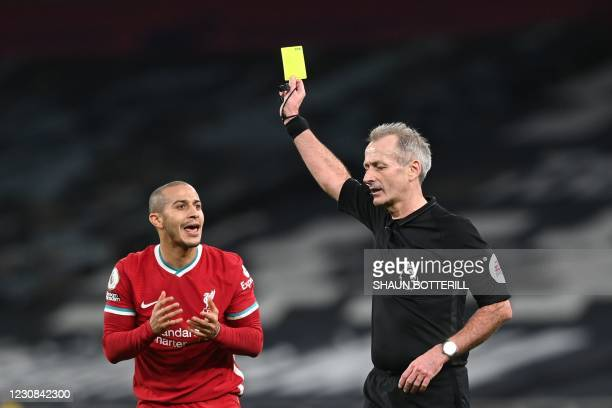 Referee Martin Atkinson shows a yellow card to Liverpool's Spanish midfielder Thiago Alcantara during the English Premier League football match...