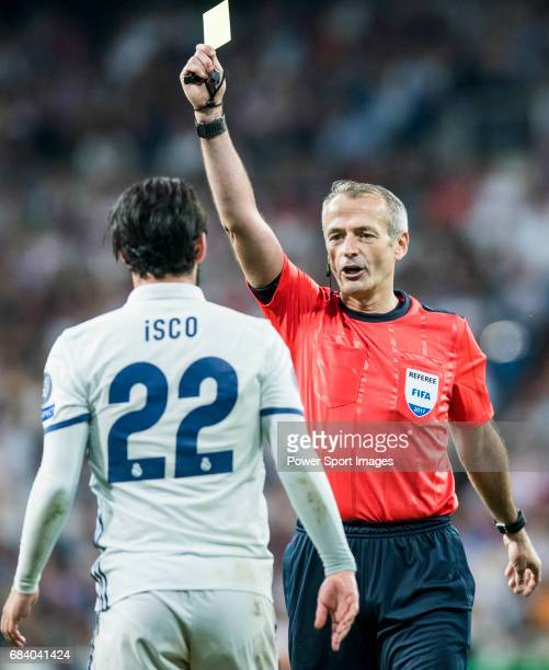 Referee Martin Atkinson shows Isco Alarcon of Real Madrid a yellow card during their 201617 UEFA Champions League Semifinals 1st leg match between...