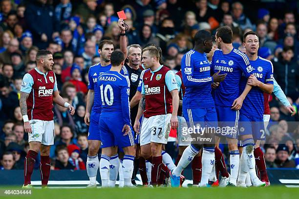 Referee Martin Atkinson shows the red card to Nemanja Matic of Chelsea for his reaction to the tackle by Ashley Barnes of Burnley during the Barclays...