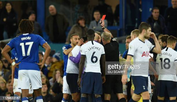 Referee Martin Atkinson shows the red card to Tottenham Hotspur's South Korean striker Son HeungMin after a foul on Everton's Portuguese midfielder...